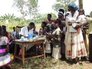Gesundheitshelferin/Krankenschwester notiert Daten, neben ihr knien und stehen viele Frauen mit Kindern/Babys.